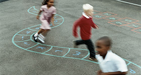 children in schoolyard playing hopscotch
